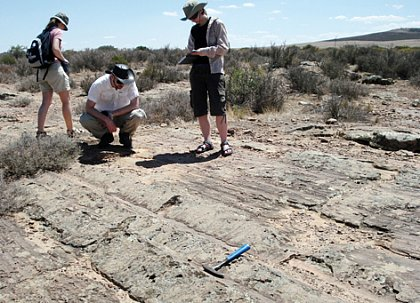 Dr. Manuela Frotzscher, Alexander Schmidt and Katharina Dietz-Laursonn gaze at the 300-million-year-old glacial groves from the Dwyka Period in Nieuwoudville, South Africa. 